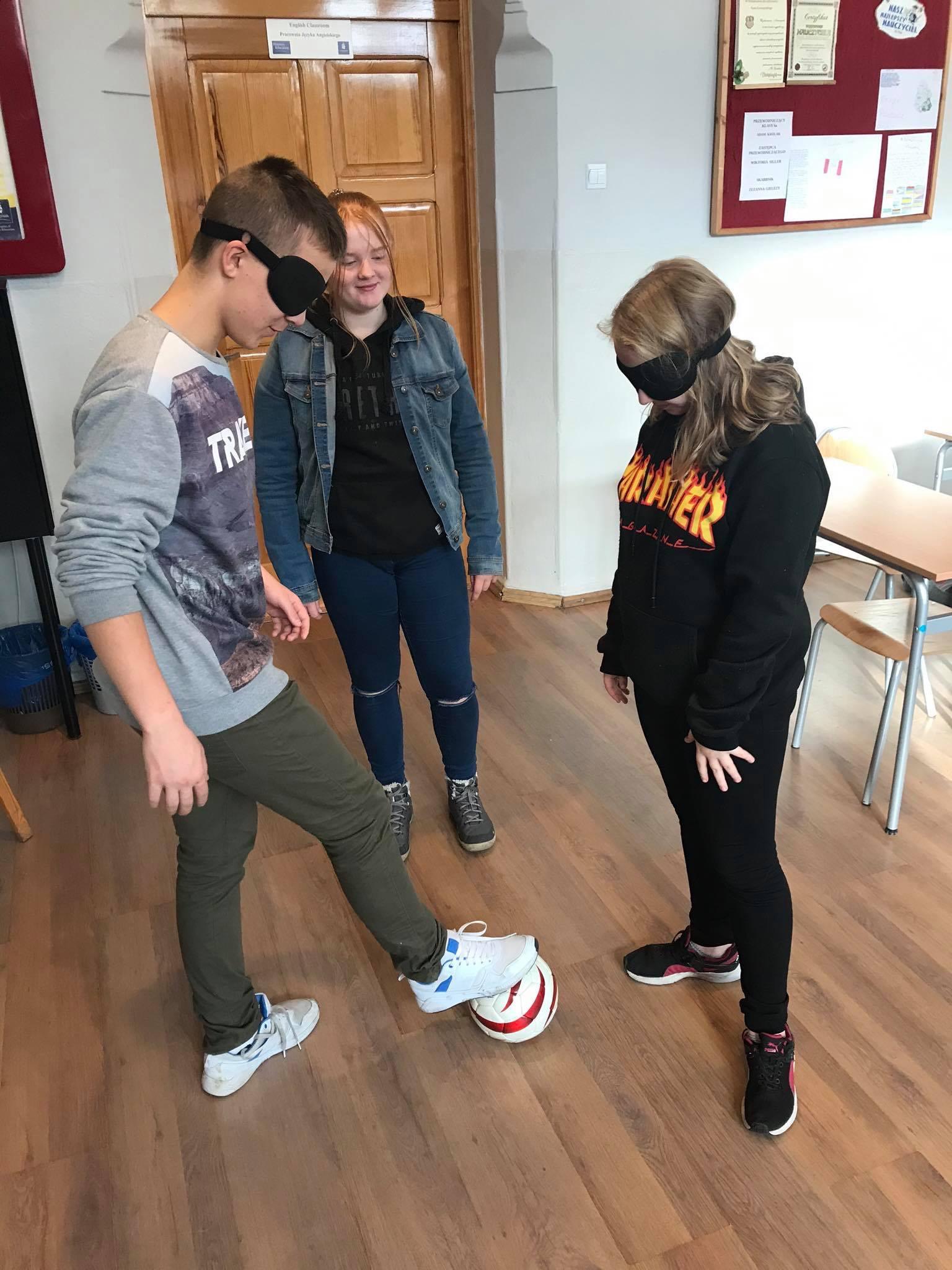 Na zdjęciu dwoje uczniów gra w piłkę nożną z zasłoniętymi oczami, w tle uczennica nadzoruje ich grę.