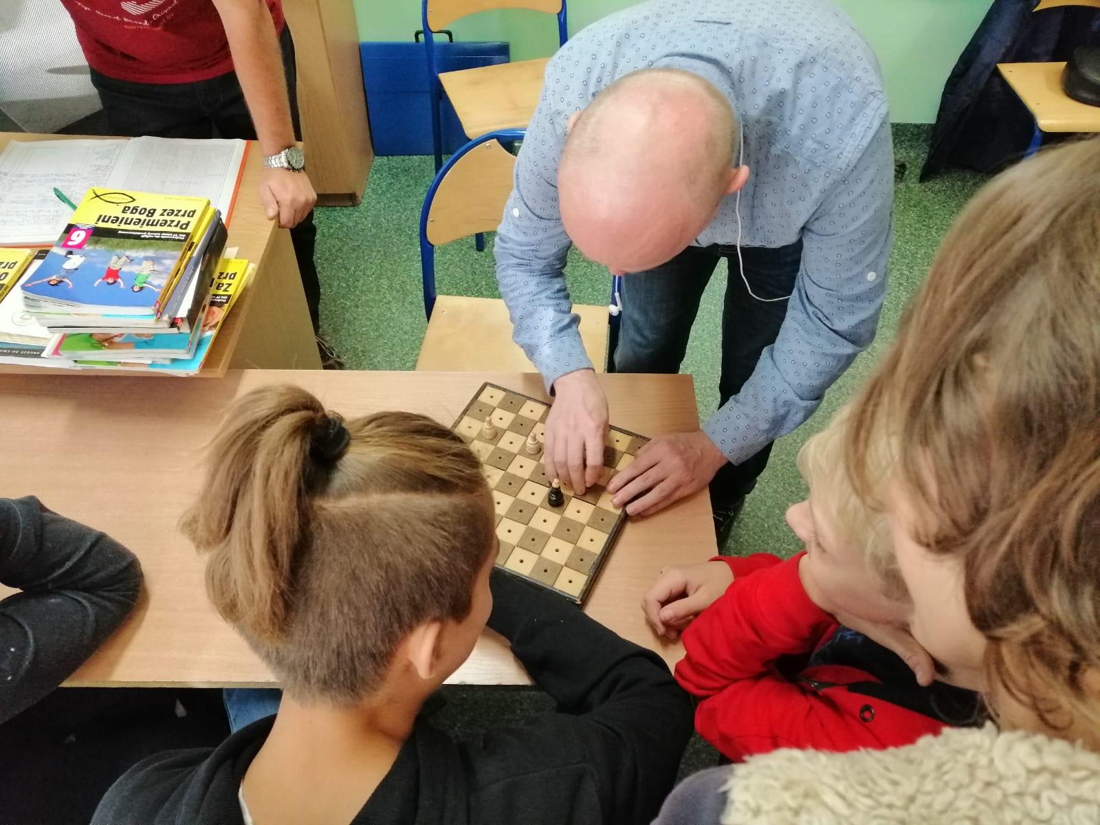 Na zdjęciu Sławek pokazuje uczniom jak grać w szachy dla niewidomych.