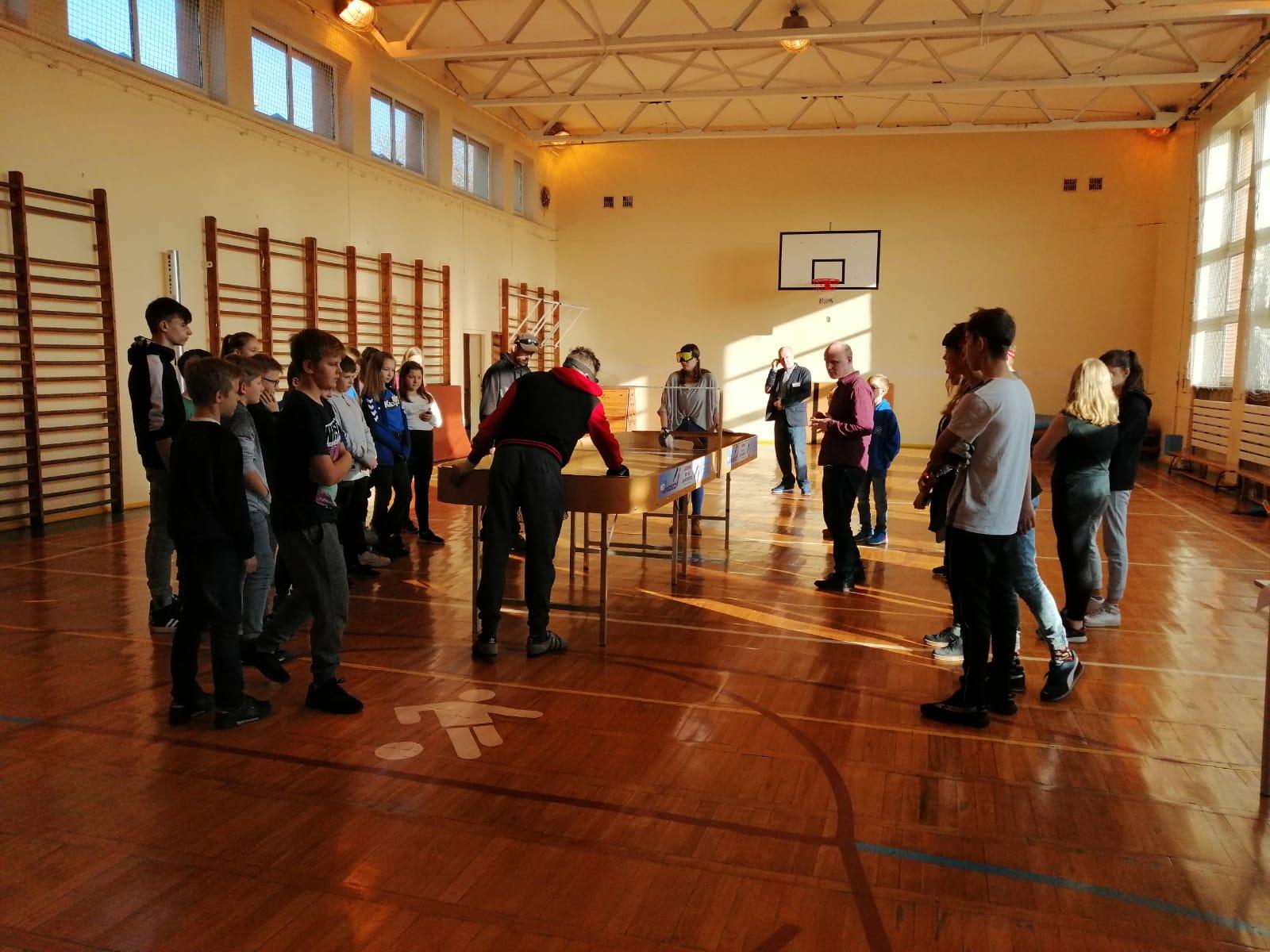 Na zdjęciu dwoje uczniów gra w showdown, kilkoro uczniów obserwuje grę, którą nadzoruje Sławomir Cywka.