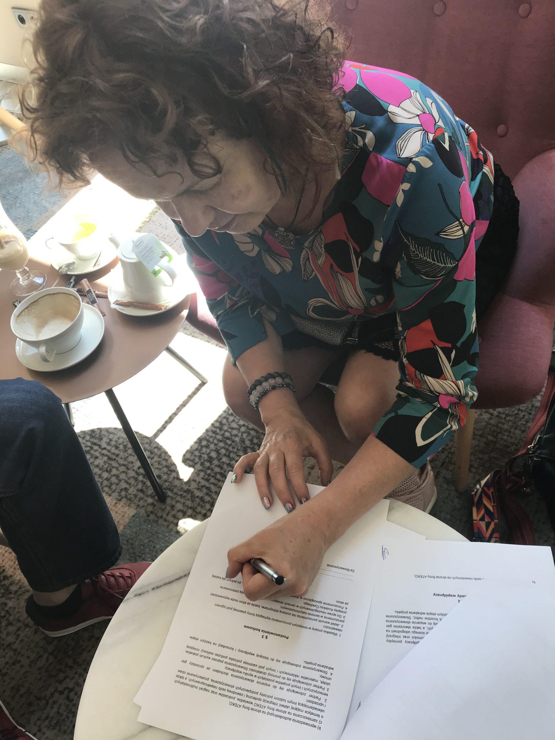 Hanna Łyczkowska podpisuje dokumenty