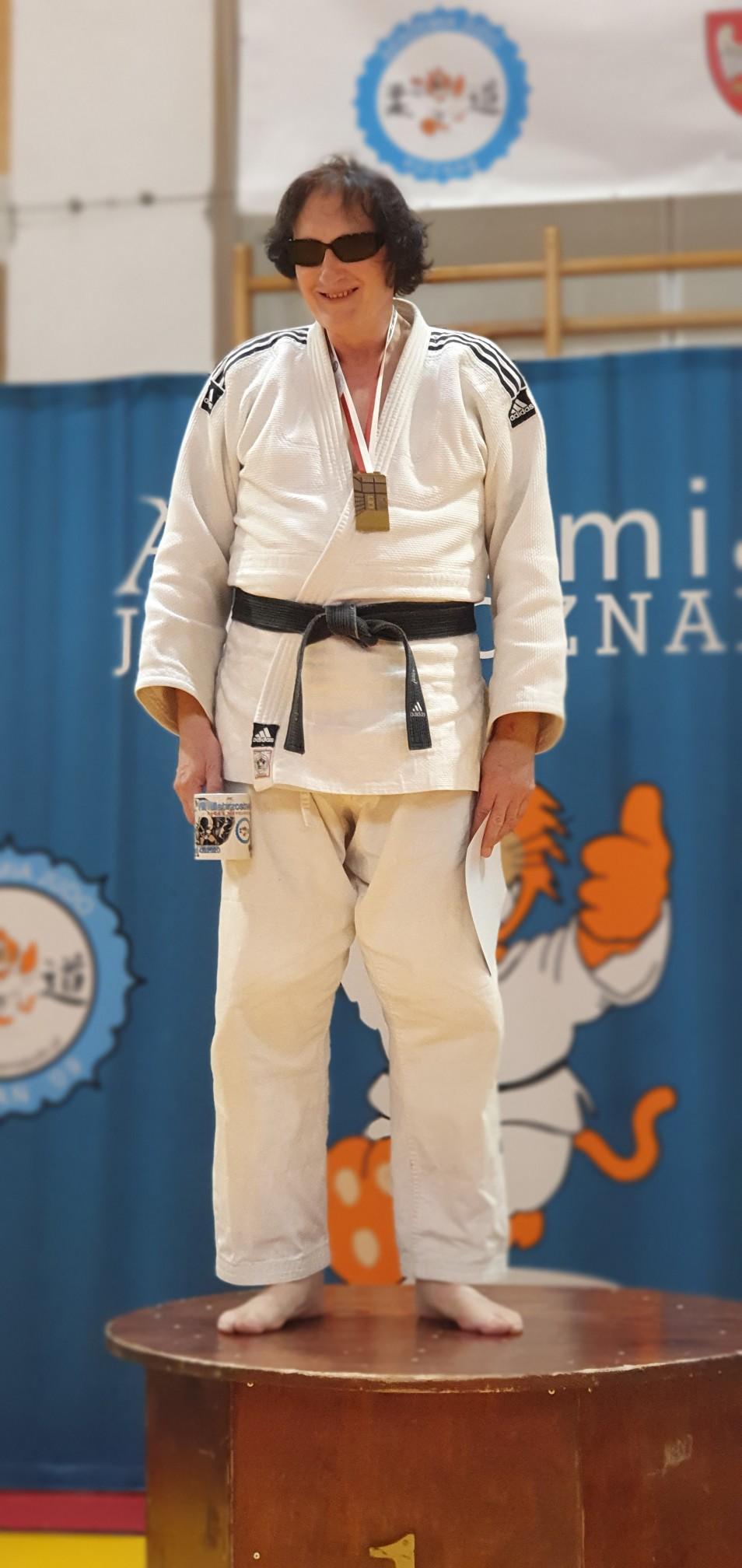 Zdjęcie Grzegorza. Grzegorz stoi na podwyższeniu, w stroju judoki i ciemnych okularach, boso, na szyi ma medal. Ręce trzyma opuszczone wzdłuż ciała, w lewej ręce trzyma kubek