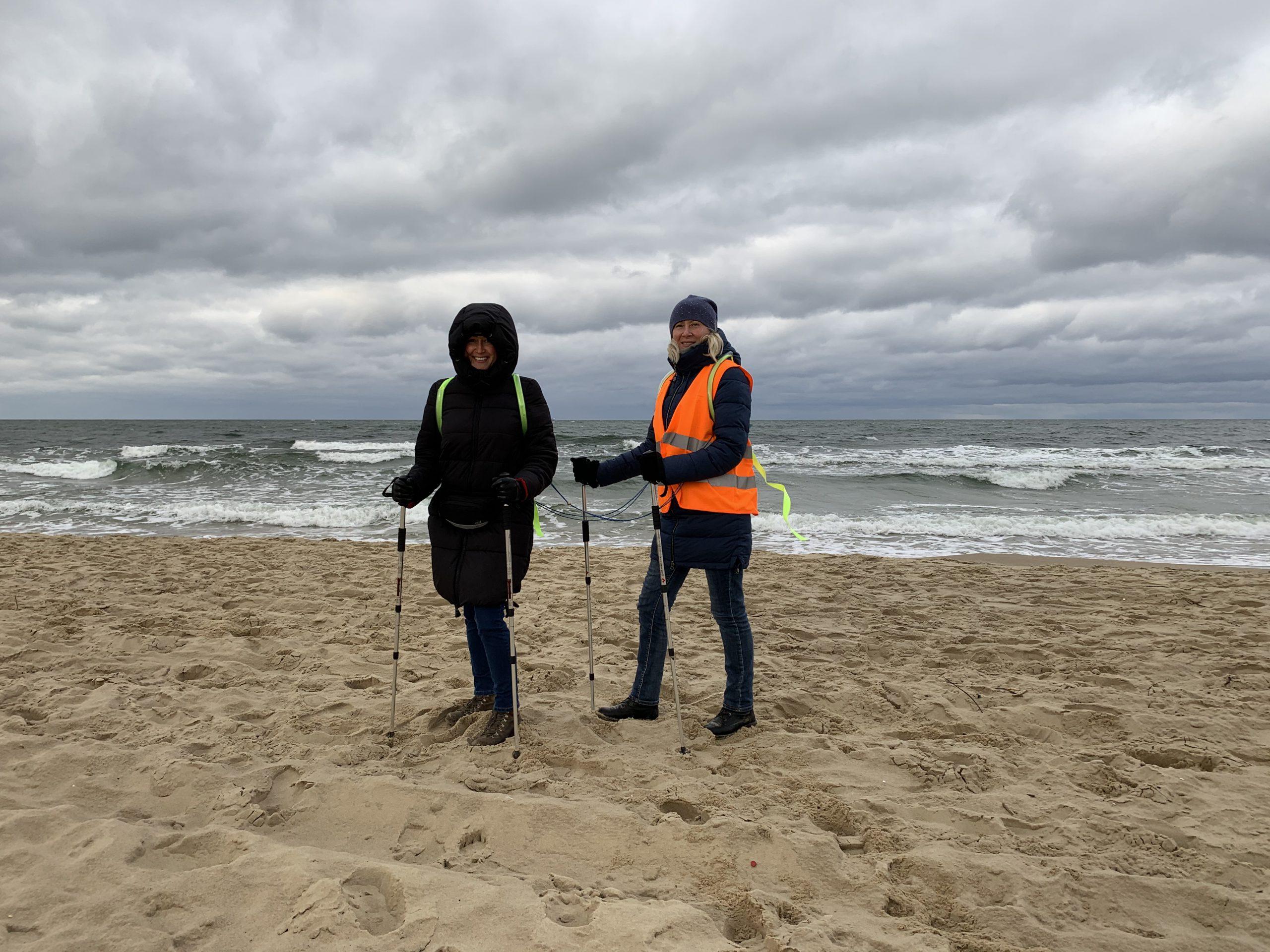 Dwie kobiety stoją na plaży, nad brzegiem morza. Są ustawione tyłem do morza, uśmiechają się. Mają na sobie długie spodnie i ciemne kurtki. Na kurtkach kamizelki odblaskowe. Obie trzymają w rękach kijki do nordic walkingu. Jedna z nich ma na głowie kaptur.