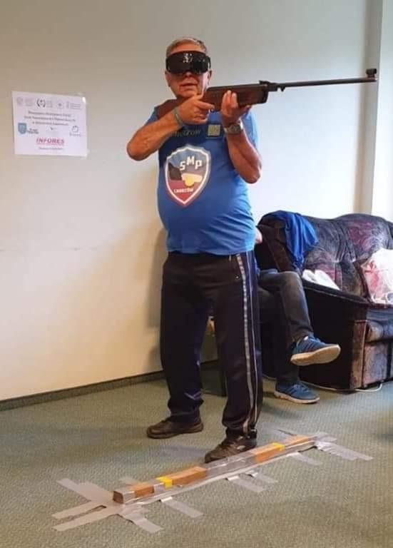 Starszy mężczyzna w goglach z bronią-długą w ręku, w koszulce klubowej SMP Chorzów przygotowany do oddania strzału